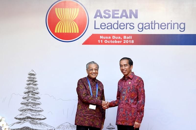 Tun Dr Mahathir Mohamad shakes hands with Indonesia's President Joko Widodo at the Asean Leaders Gathering in Bali October 11, 2018. — Bernama pic