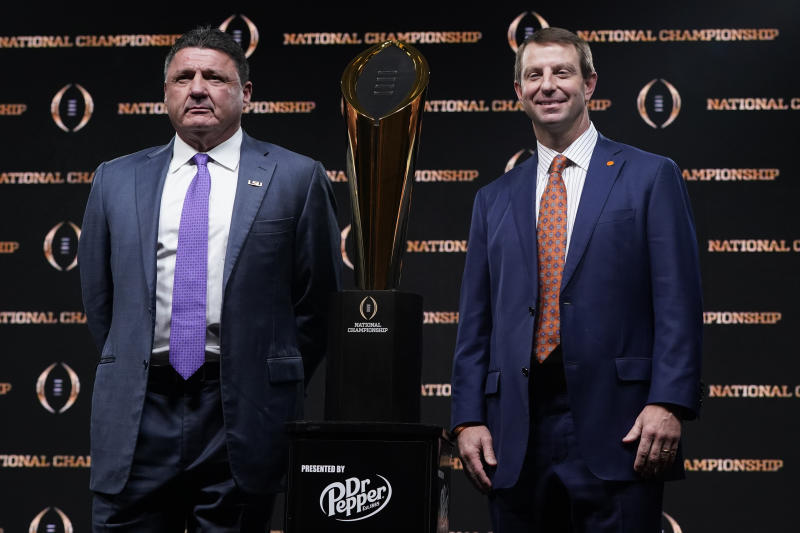 LSU head coach Ed Orgeron, left, and Clemson head coach Dabo Swinney pose with the trophy after a news conference for the NCAA College Football Playoff national championship game Sunday, Jan. 12, 2020, in New Orleans. Clemson is scheduled to play LSU on Monday. (AP Photo/David J. Phillip)