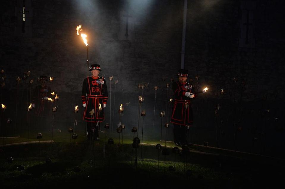 <p>Beefeaters lighting the first of thousands of flames in a lighting ceremony in the dry moat of the Tower of London as part of an installation called Beyond the Deepening Shadow: The Tower Remembers, to mark the centenary of the end of First World War. (Picture: PA) </p>