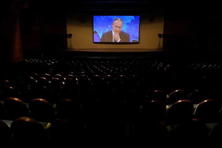 Russian President Vladimir Putin appears on a screen in a hall at the World Trade Centre's congress centre as he holds his annual press conference via a video link from the Novo-Ogaryovo state residence, in Moscow