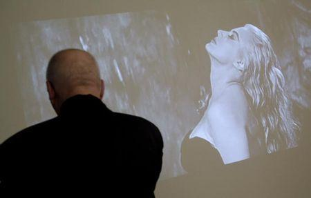 """A visitor looks at Swedish actress Anita Ekberg playing in Federico Fellini's movie """"La Dolce Vita"""" displayed as part of an exhibition at Rome's Macro Museum October 29, 2010. REUTERS/Alessia Pierdomenico"""
