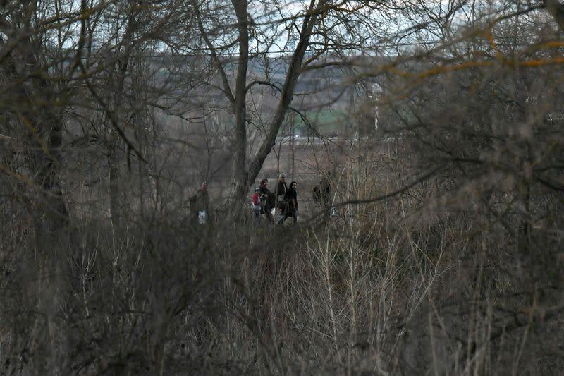 Migrants walk next to the Evros river on the Turkish side of the Greek-Turkish border, as seen from near the village of Marasia