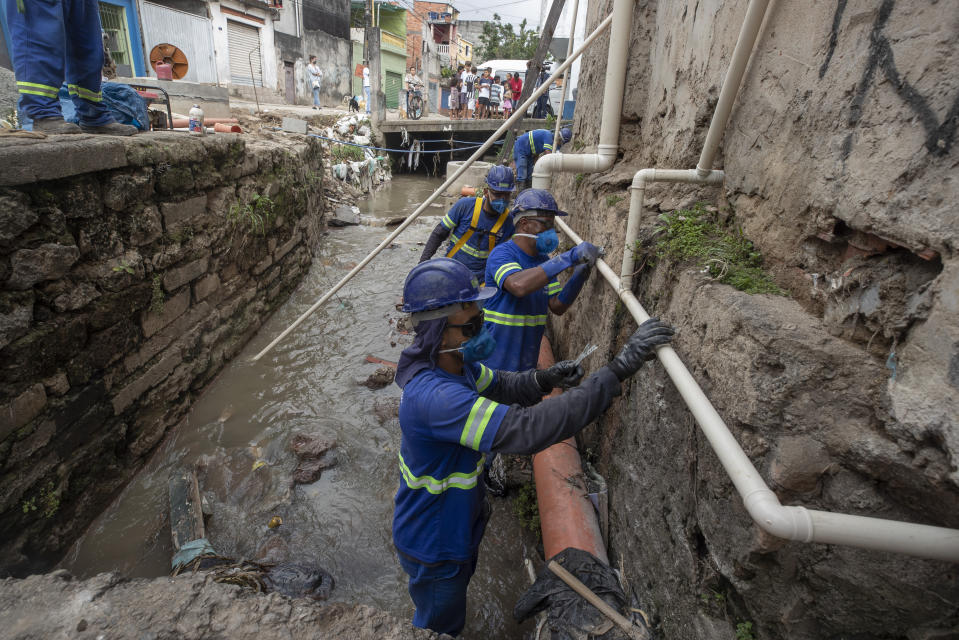 Men work to install a sewage system at the Americanopolis community, located near the Pinheiros River in Sao Paulo, Brazil, Thursday, Oct. 22, 2020. Affected by domestic sewage and solid wastes discharges for years, Sao Paulo's state government is again trying to clean the Pinheiros River, considered one of the most polluted in Brazil. (AP Photo/Andre Penner)