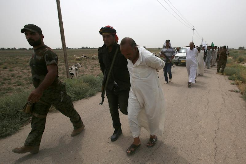 Iraqi pro-government militiamen escort men detained for investigation after the liberation from Islamic State (IS) militants of the village of Sayed Ghareeb, near Dujail, some 70 kilometres north of Baghdad on June 2, 2015 (AFP Photo/Mohammed Sawaf)