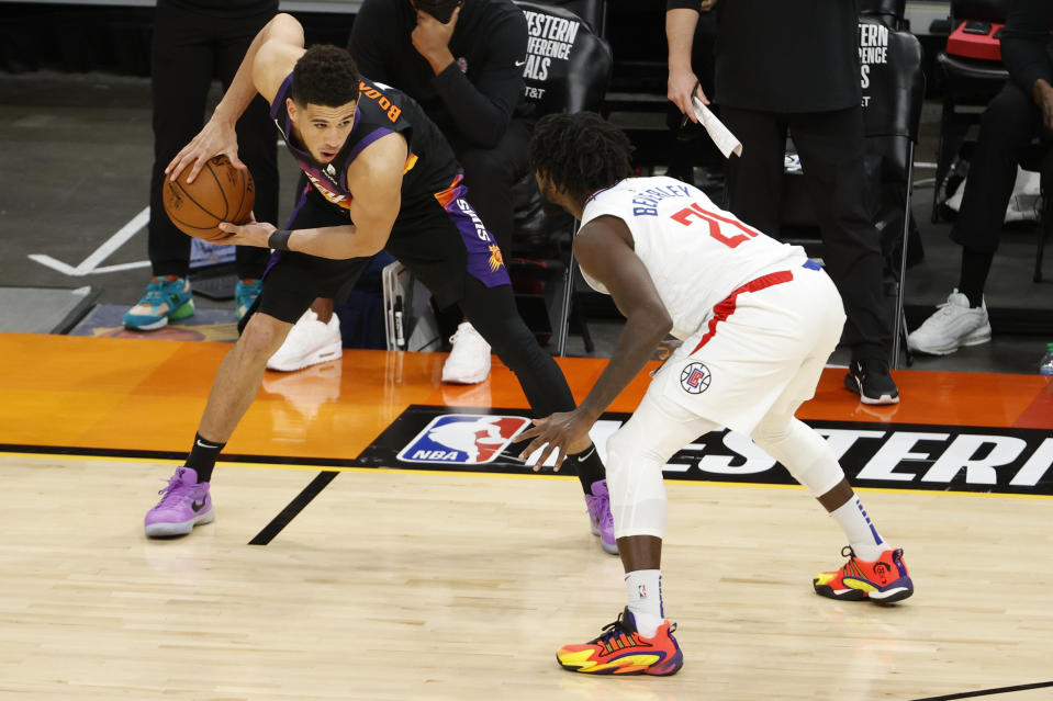 Devin Booker of the Phoenix Suns controls the ball ahead of Patrick Beverley of the LA Clippers