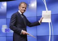 FILE- In this Wednesday, March 29, 2017 file photo, EU Council President Donald Tusk holds British Prime Minister Theresa May's Brexit letter in notice of the UK's intention to leave the bloc under Article 50 of the EU's Lisbon Treaty at a press conference in Brussels. Britain and the European Union have struck a provisional free-trade agreement that should avert New Year's chaos for cross-border commerce and bring a measure of certainty to businesses after years of Brexit turmoil. The breakthrough on Thursday, Dec. 24, 2020 came after months of tense and often testy negotiations that whittled differences down to three key issues: fair-competition rules, mechanisms for resolving future disputes and fishing rights. (AP Photo/Olivier Matthys, File)