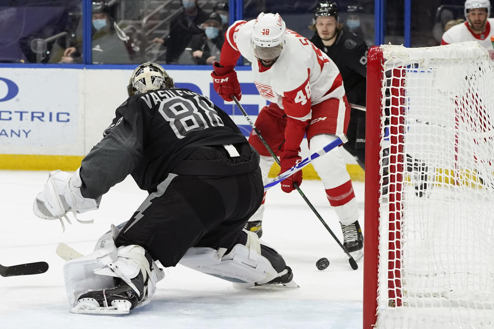 Detroit Red Wings left wing Givani Smith (48) tries to get off a shot on Tampa Bay Lightning goaltender Andrei Vasilevskiy (88) during the first period of an NHL hockey game Saturday, April 3, 2021, in Tampa, Fla. (AP Photo/Chris O'Meara)