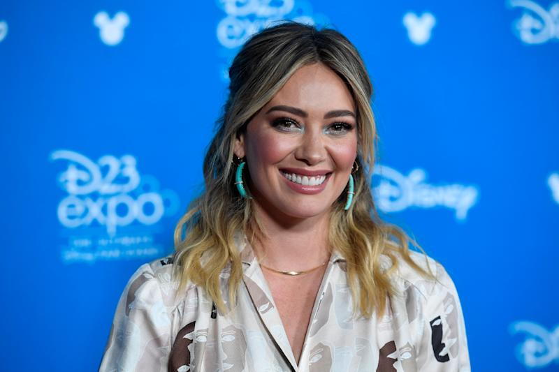 Hilary Duff smiles while posing at the D23 expo