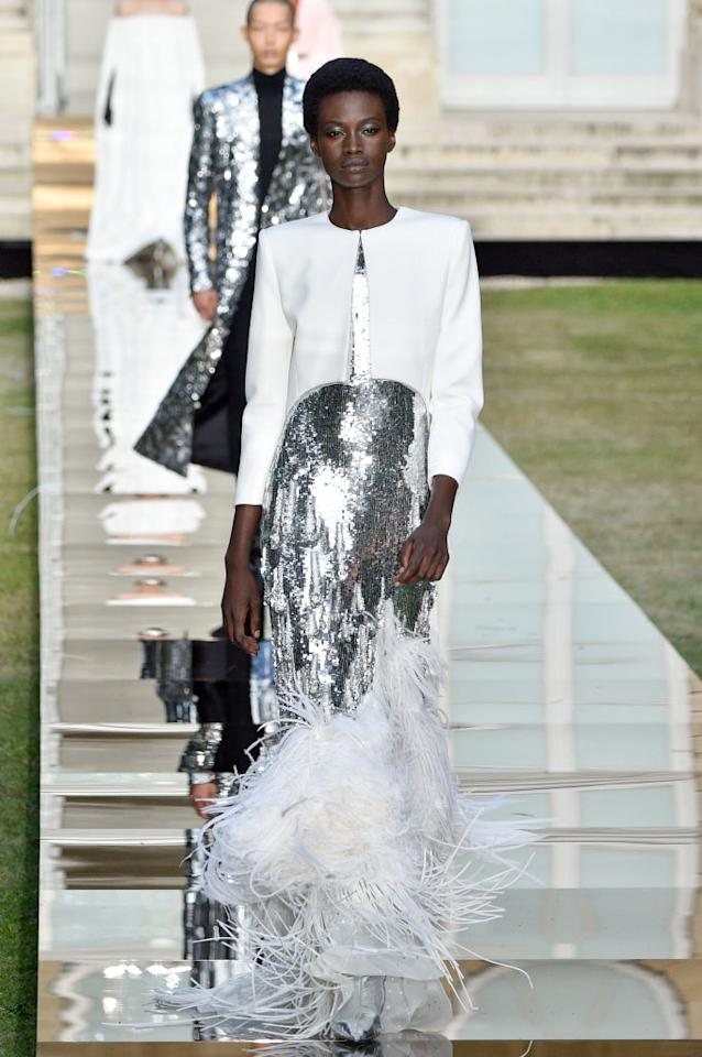 <p>Model wears a metallic silver sequin bodice gown with white feathers and a white capelet from the Givenchy fall 2018 couture collection. (Photo: Getty Images) </p>
