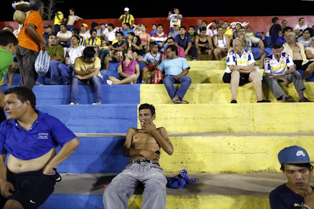 In this Oct. 18, 2014 photo, fans of the Deportivo Capiata soccer team watch a national league match against Cerro Porteno in Capiata, Paraguay. Capiata has a tiny fan base, and everything about the club is modest: its dressing room, workout room and stadium amenities. (AP Photo/Jorge Saenz)