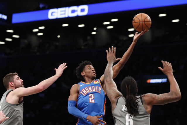 Oklahoma City Thunder guard Shai Gilgeous-Alexander (2) goes up for two points as Brooklyn Nets guard Joe Harris, left, and Nets center DeAndre Jordan (6) defend the shot during the first half of an NBA basketball game, Tuesday, Jan. 7, 2020, in New York. (AP Photo/Kathy Willens)