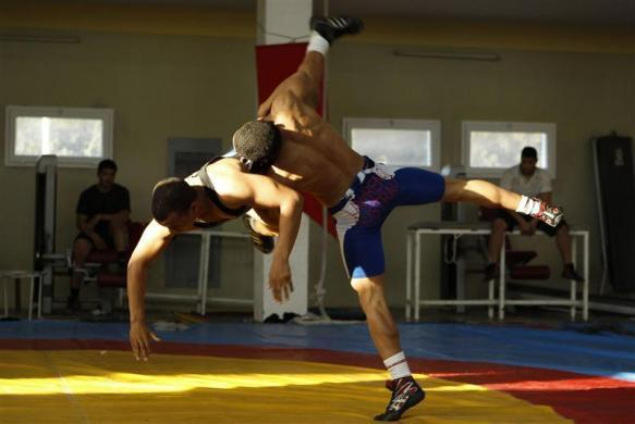 Tunisian wrestler Haithem Belaiech (in blue) trains for the 2012 London Olympic Games in Tunis, March 29, 2012.