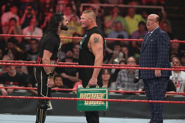 Paul Heyman looks on as Brock Lesnar and Seth Rollins taunt one another. (Photo courtesy of WWE)