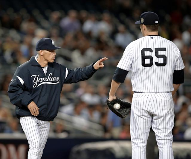 New York Yankees manager Joe Girardi calls for a new pitcher in the third inning asstarting pitcher Phil Hughes stands on the mound in a baseball game against the Tampa Bay Rays, Wednesday, Sept. 25, 2013, in New York. (AP Photo/Kathy Willens)