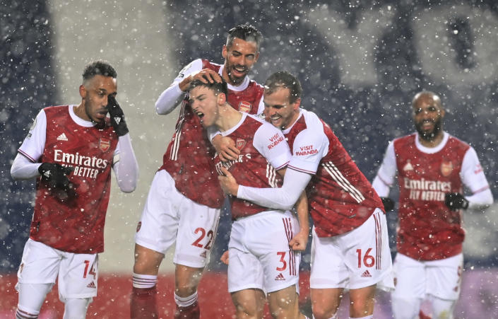 Arsenal's Kieran Tierney, (3), celebrates with teammates after scoring the opening goal of the game as snow falls during the English Premier League soccer match between West Bromwich Albion and Arsenal at the Hawthorns in Birmingham, England, Saturday, Jan. 2, 2021. (Michael Regan/ Pool via AP)