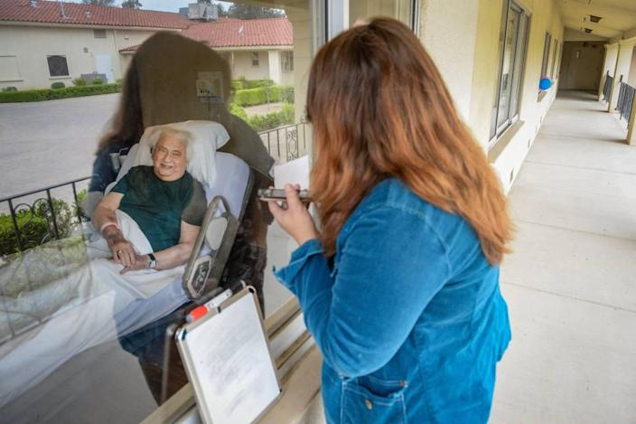Denise Plank talks on her cell phone with her father, Ed, 84, while visiting him through his nursing home window at the California Armenian Home in Fresno on Friday, April 17, 2020. Ed is suffering from a blood disease but Denise continues to visit him nearly every day, if only through his nursing home window.