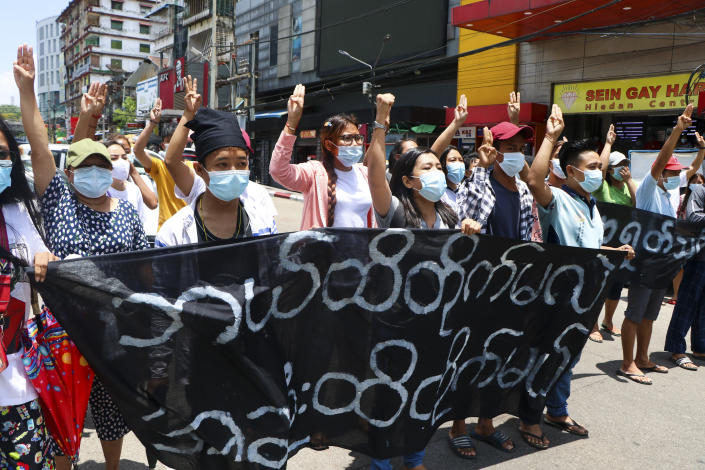 "Anti-coup protesters flashes the three-finger salute of defiance and chant slogans with banners that read; '' The Kamayut strike will be fight for to the end when we get victory."" during the demonstration against the military coup at Kamayut township Yangon, Monday, May 3, 2021. (AP Photo)"