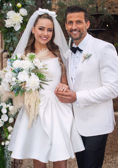 A photo of Tim Robards wearing a white tuxedo jacket and April Rose Pengilly wearing a white wedding dress on set of their wedding on Neighbours.