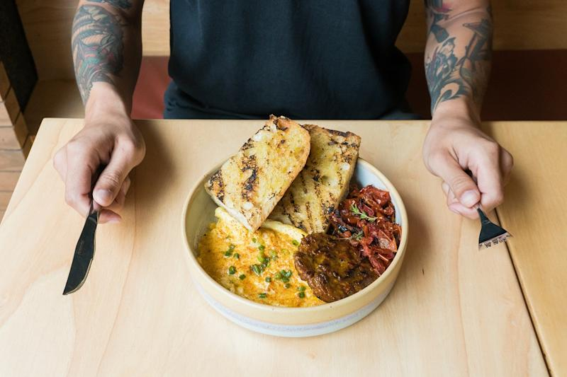 A customizable 'breakfast bowl' featuring grilled focaccia, scrambled egg, sai-ua patty and roasted tomatoes.