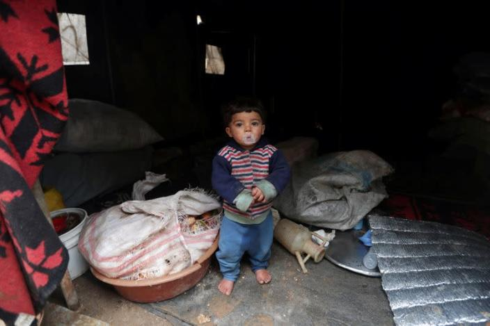Internally displaced child looks out from a tent in Azaz