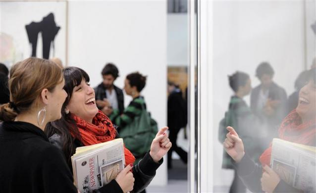Women look at an exhibit by the artist Damien Hirst at the Frieze Art Fair in London October 14, 2010.