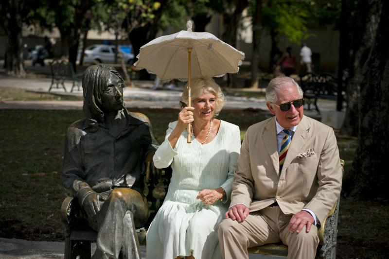 Prince Charles and his wife Camilla, Duchess of Cornwall, sit on a park bench next to a statue depicting John Lennon as they pose for photos, during a cultural event in Havana, Cuba, Tuesday, March 26, 2019. The heir to the British throne arrived in Cuba Sunday with an agenda including visits to historic sites, a solar park, organic farm, bio-medical research center, a meeting with entrepreneurs, a cultural gala and a dinner with Cuba's president. (AP Photo/Ramon Espinosa)