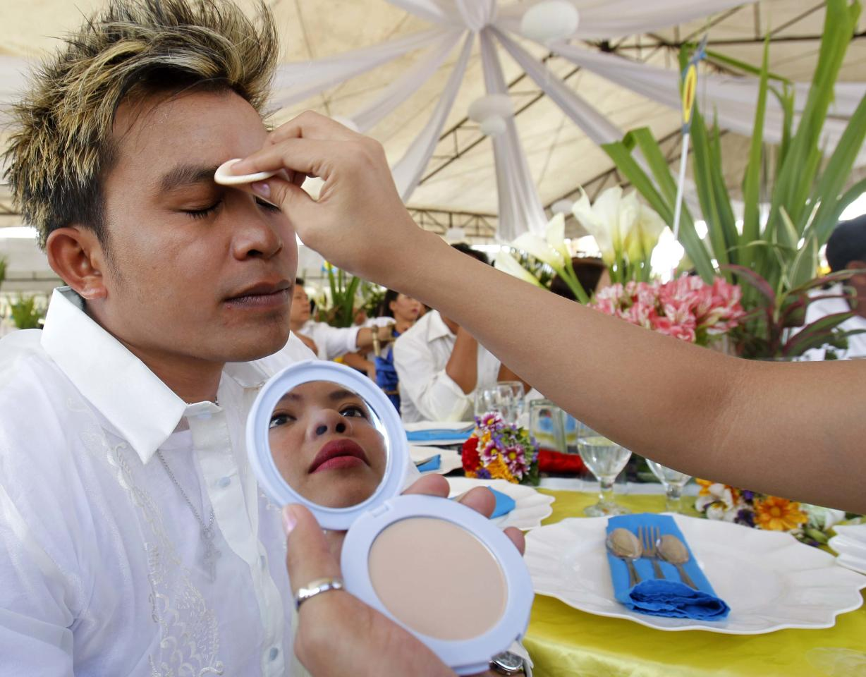 A bride is seen reflected in a mirror as she applies face powder on her groom before a Valentine's Day mass wedding organized by the government's Home Development Mutual Fund in Marikina City, Metro Manila, February 14, 2013. More than 3000 couples were simultaneously married nationwide. REUTERS/Cheryl Ravelo (PHILIPPINES - Tags: SOCIETY)