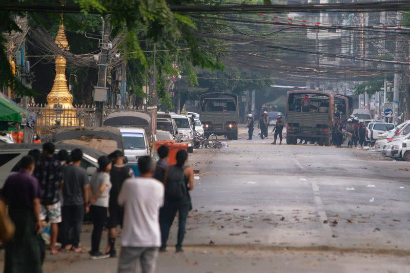 People look at a police vehicle after Sanchaung district has been seized in search of anti-coup demonstrators in Yangon