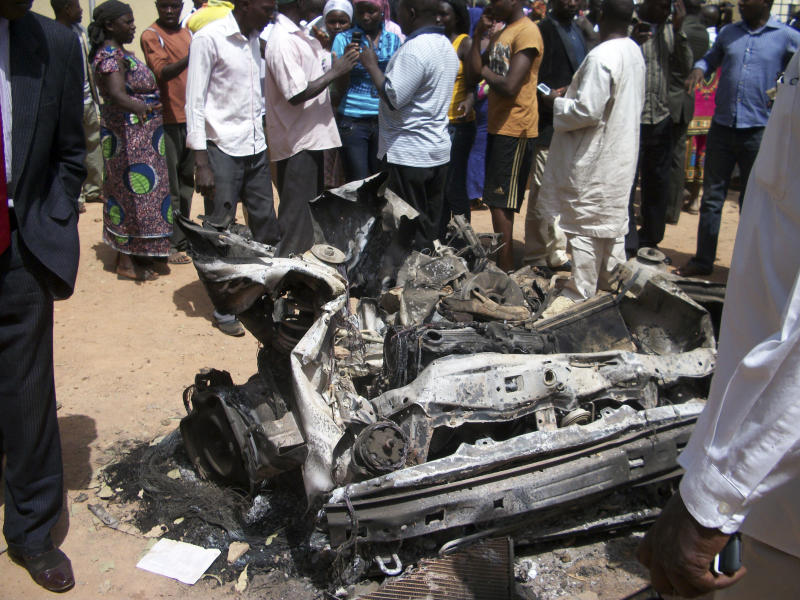 People gather around a car used by a suicide bomber at a catholic church in Jos, Nigeria, on Sunday, March 11, 2012.  A suspected suicide attack hit a Catholic church in the central Nigerian city of Jos on Sunday, killing three people, the National Emergency Management Agency (NEMA) said. (AP Photos)