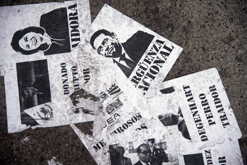"""Glued printouts of Guatemalan President Jimmy Morales, top center, and Foreign Minister Sandra Jovel and the Spanish words: """"National shame. Trader. Liars. Dog."""" cover the ground outside the Constitutional Court in Guatemala City, Wednesday, Jan. 9, 2019. Guatemala's highest court has blocked President Jimmy Morales' decision to unilaterally end the United Nations International Commission Against Impunity, CICIG. (AP Photo/Santiago Billy)"""