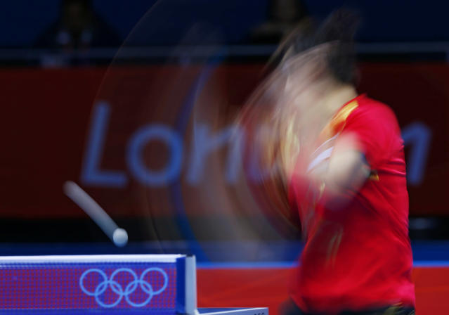 Singapore's Feng Tianwei hits a return to South Korea's Kim Kyungah in their women's team bronze medal table tennis singles match at the ExCel venue during the London 2012 Olympic Games August 7, 2012. Picture taken on slow shutter. REUTERS/Darren Staples (BRITAIN - Tags: OLYMPICS SPORT TABLE TENNIS)