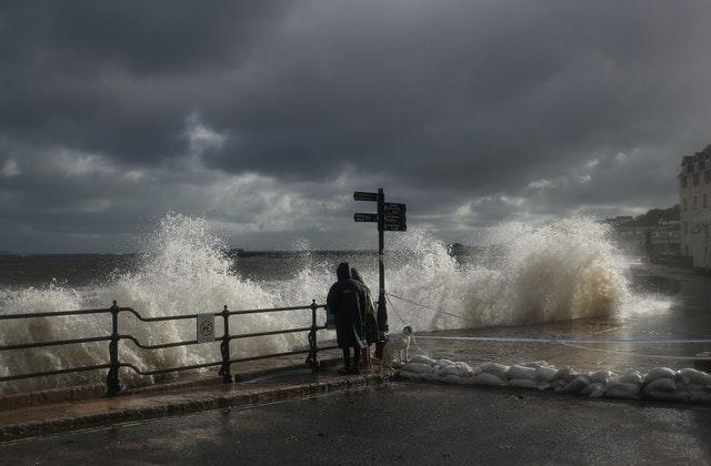 People watch the spectacle as waves crash along the coast at Swanage