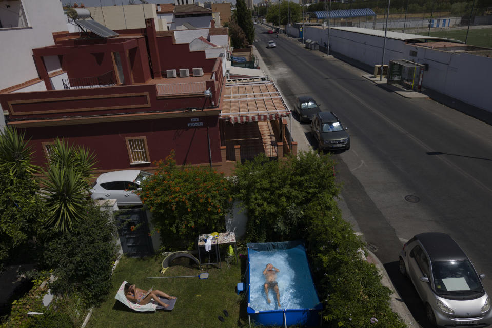 "Javier Salcedo swims in a portable plastic pool as his wife Irene Blanco sunbathes in their garden in Seville, Spain on August 13, 2020. ""We decided to buy it second hand and a week later a heat wave started and all the pools were sold out. I could see that would happen"". ( AP Photo/ Laura Leon)"