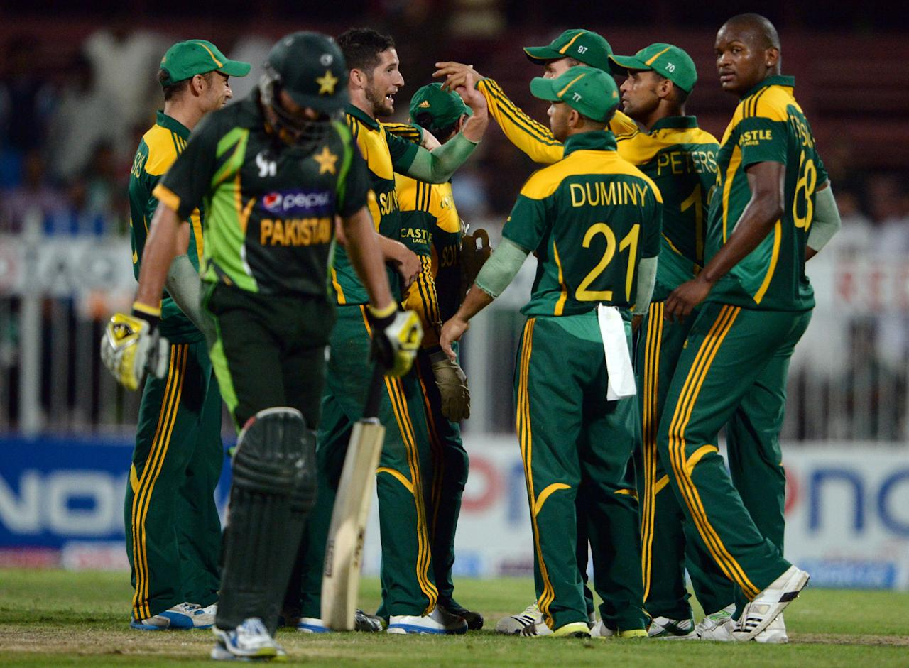 South African cricketers celebrate after taking wicket of Pakistan's batsman Shahid Afridi (2nd L) during the fifth and final day international at Sharjah Cricket Stadium in Sharjah on November 11, 2013. Pakistan were chasing a challenging 268-run target after South African skipper AB de Villiers samshed a 102-ball 115 not out in his team's 268-7 run total. South Africa lead the five-match series 3-1.AFP PHOTO/ASIF HASSAN        (Photo credit should read ASIF HASSAN/AFP/Getty Images)