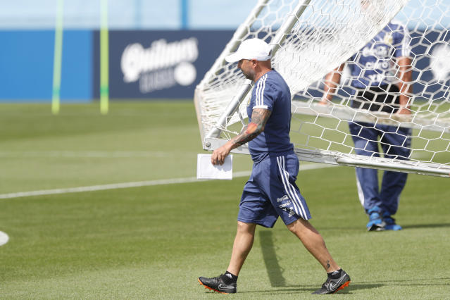 Coach Jorge Sampaoli helps ground staff move a goal prior to a training session of Argentina at the 2018 soccer World Cup in Bronnitsy, Russia, Sunday, June 24, 2018. (AP Photo/Ricardo Mazalan)
