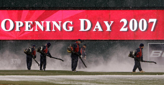 FILE - In this April 6, 2007, file photo, members of the Jacobs Field grounds crew use leaf blowers to clear snow from the field during a delay in the top of the fifth inning of a baseball game between the Seattle Mariners and the Cleveland Indians, on opening day in Cleveland. To baseball fans, opening day is an annual rite of springthat evokes great anticipation and warm memories. This year's season was scheduled to begin Thursday, March 26, 2020, but there will be no games for a while because of the coronavirus outbreak. (AP Photo/Mark Duncan, File)