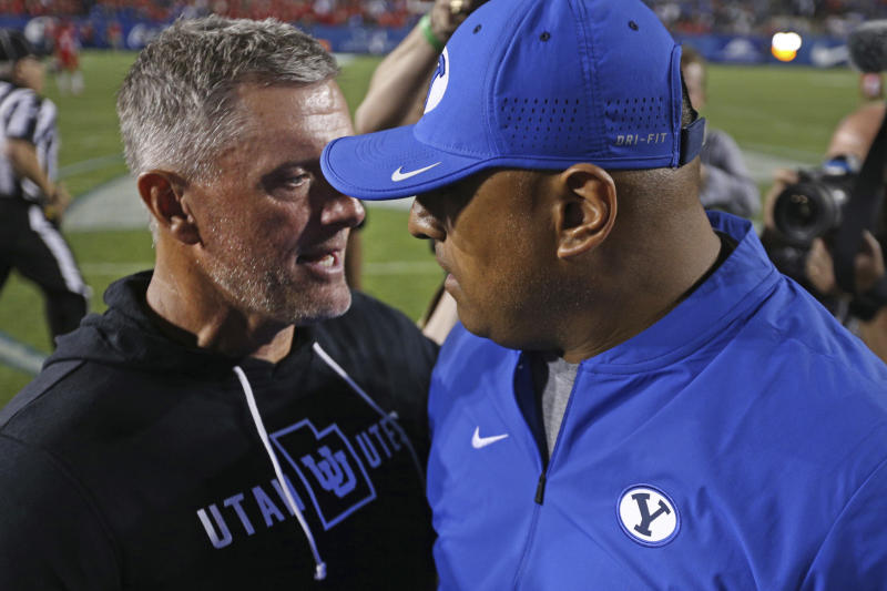 Utah head coach Kyle Whittingham, left, and BYU head coach Kalani Sitake greet each other after an NCAA college football game, Thursday, Aug. 29, 2019, in Provo, Utah. Utah defeated BYU 30-12. (AP Photo/George Frey)