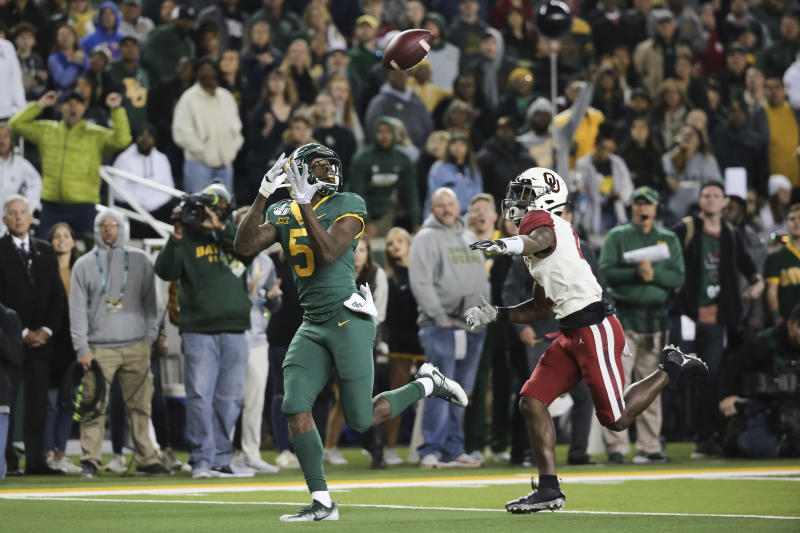 Baylor wide receiver Denzel Mims, left, waits the ball on a 30-yard touchdown catch as Oklahoma cornerback Jaden Davis, right, defends during the first half of an NCAA college football game in Waco, Texas, Saturday, Nov. 16, 2019. (AP Photo/Ray Carlin)
