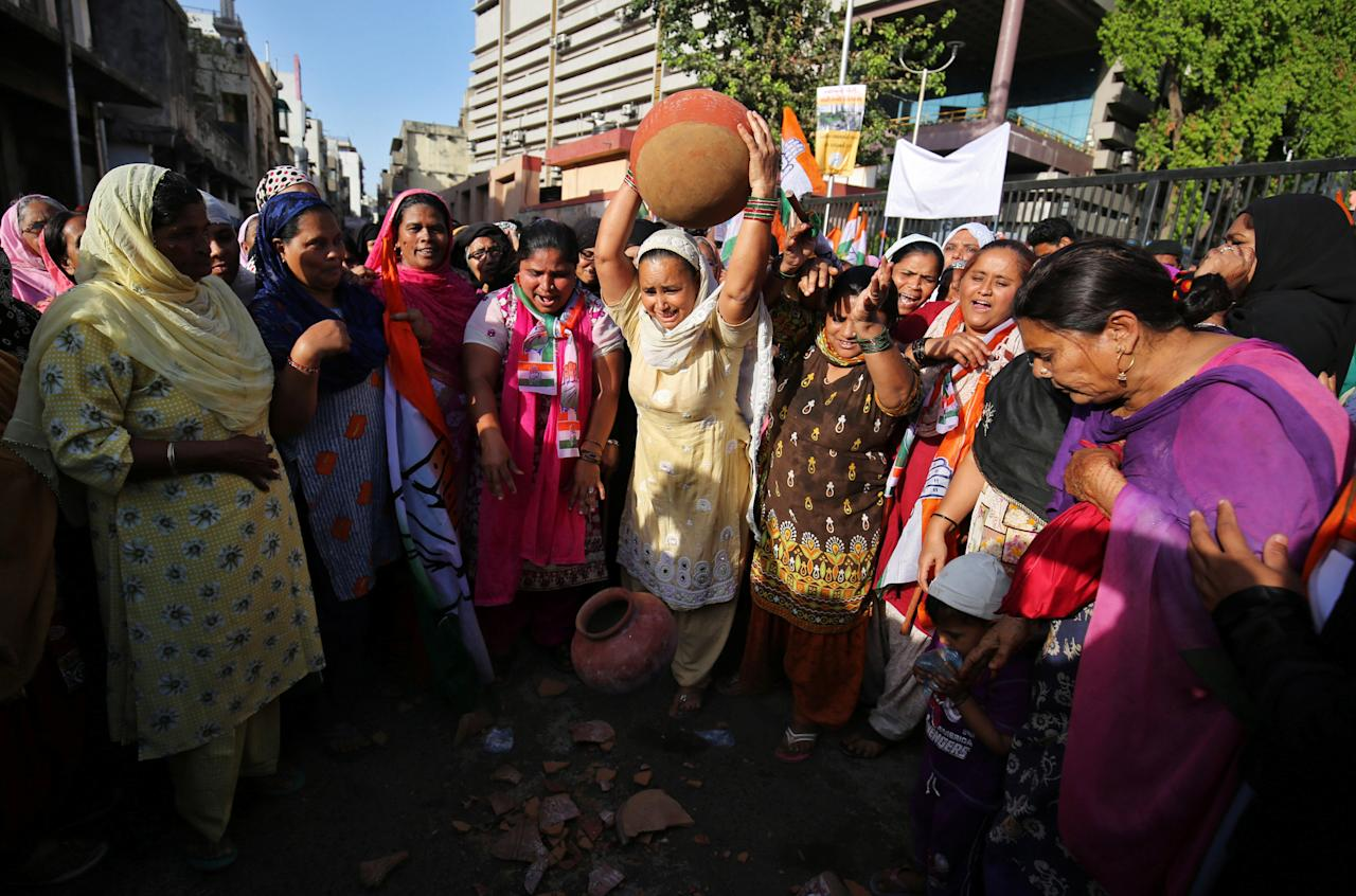 Residents throw earthen pitchers onto the ground in protest against the shortage of drinking water outside the municipal corporation office in Ahmedabad India, March 15, 2018. REUTERS/Amit Dave