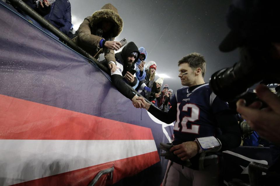 New England Patriots quarterback Tom Brady shakes hands with a fan as he leaves the field after losing an NFL wild-card playoff football game to the Tennessee Titans, Saturday, Jan. 4, 2020, in Foxborough, Mass. (AP Photo/Charles Krupa)