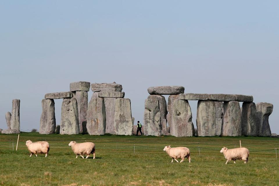 Sheep graze as security guards patrol the prehistoric monument at Stonehenge in southern England. Source: Getty