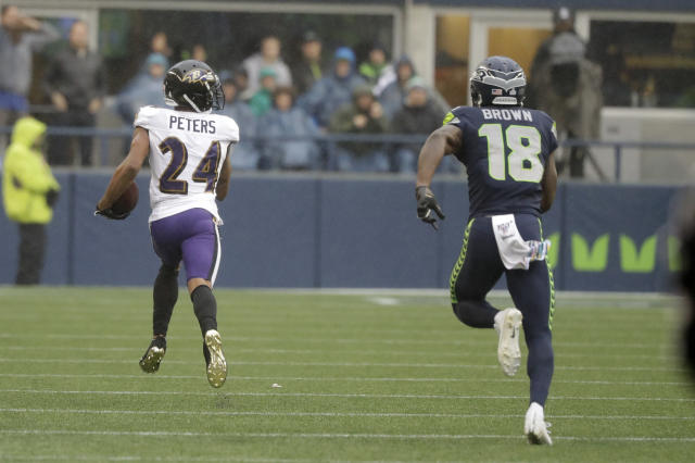 Baltimore Ravens cornerback Marcus Peters (24) runs for a touchdown after he intercepted a pass intended for Seattle Seahawks wide receiver Jaron Brown (18) during the first half of an NFL football game, Sunday, Oct. 20, 2019, in Seattle. (AP Photo/Elaine Thompson)