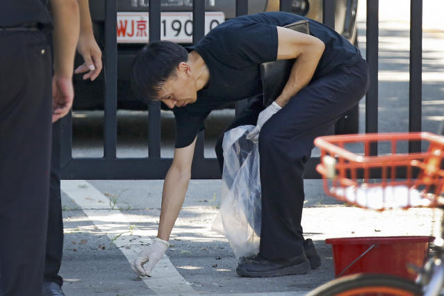 <p>A crime scene policeman collects fragments at the site of an explosion outside the U.S. Embassy in Beijing, Thursday, July 26, 2018. (Photo: Andy Wong/AP) </p>