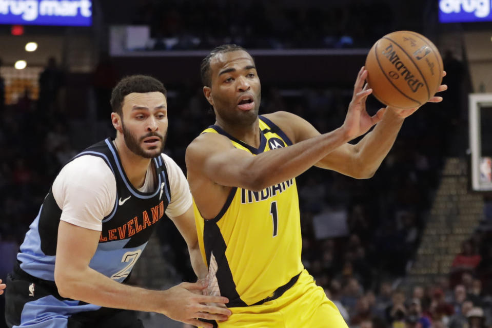 Indiana Pacers' T.J. Warren (1) passes against Cleveland Cavaliers' Larry Nance Jr. (22) in the second half of an NBA basketball game, Saturday, Feb. 29, 2020, in Cleveland. Indiana won 113-104. (AP Photo/Tony Dejak)