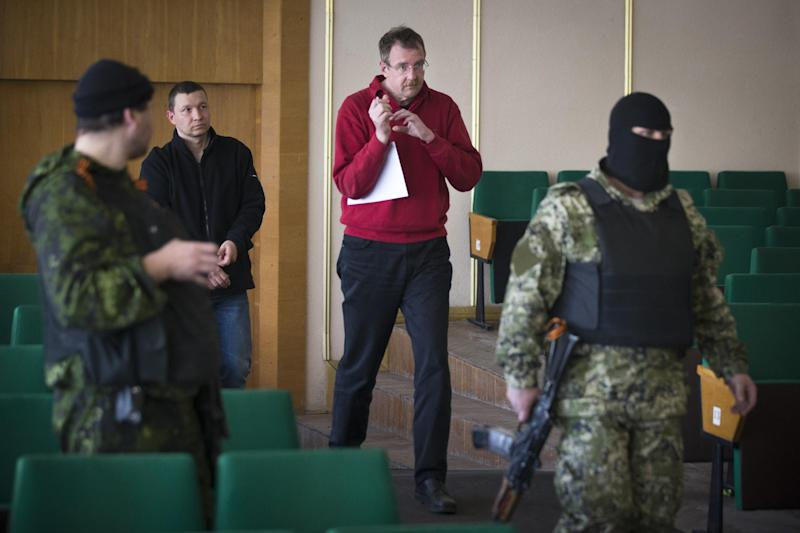 Axel Schneider of Germany, in red 2nd right, of foreign military observers is escorted by pro-Russian militants to attend a press conference in city hall, of Slovyansk, eastern Ukraine, Sunday, April 27, 2014. As Western governments vowed to impose more sanctions against Russia and its supporters in eastern Ukraine, a group of foreign military observers remained in captivity Saturday accused of being NATO spies by a pro-Russian insurgency. The German-led, eight-member team was traveling under the auspices of the Organization of Security and Cooperation in Europe when they were detained Friday. (AP Photo/Alexander Zemlianichenko)