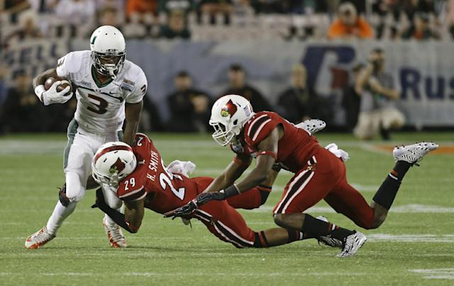 Miami wide receiver Stacy Coley (3) tries to get away from Louisville safety Hakeem Smith (29) and safety Jermaine Reve, right, after a reception during the first half of the Russell Athletic Bowl NCAA college football game in Orlando, Fla., Saturday, Dec. 28, 2013.(AP Photo/John Raoux)