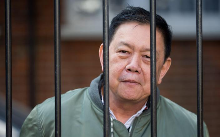 Former Myanmar Ambassador Kyaw Zwar Minn speaks to media through the locked gates of his official residence on the day he is set to be evicted. - Jamie Lorriman for The Telegraph