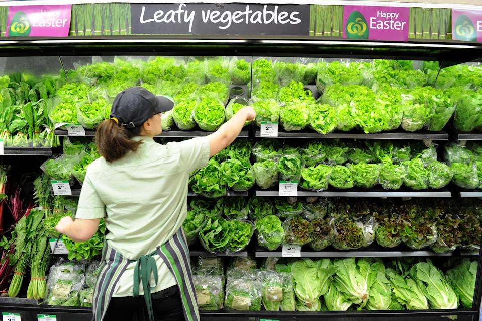 An employee arranges lettuces on display inside a Woolworths grocery store in Brisbane.