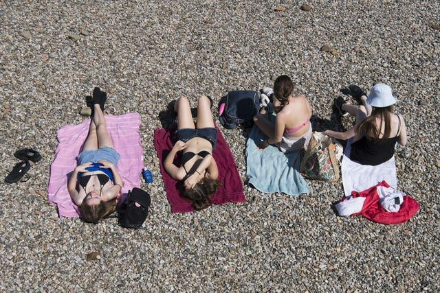 People sunbathe on the river bank in central London