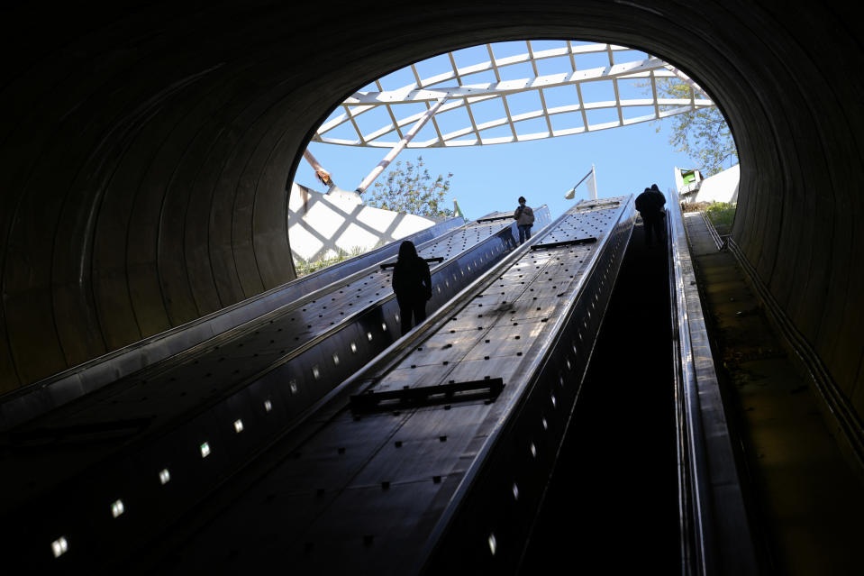 People ride escalators at Washington Metro's Dupont Circle station, Friday, April 23, 2021, in Washington. As President Joe Biden urges more federal spending for public transportation, transit agencies decimated by COVID-19 are struggling with a new uncertainty: how to win passengers back. (AP Photo/Patrick Semansky)